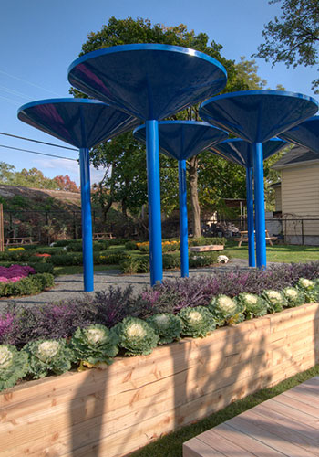 """Sculptural rainwater collection towers amidst planting beds at the Curtis """"50-Cent"""" Jackson Community Gardens in Queens, NY / New York Restoration Project"""