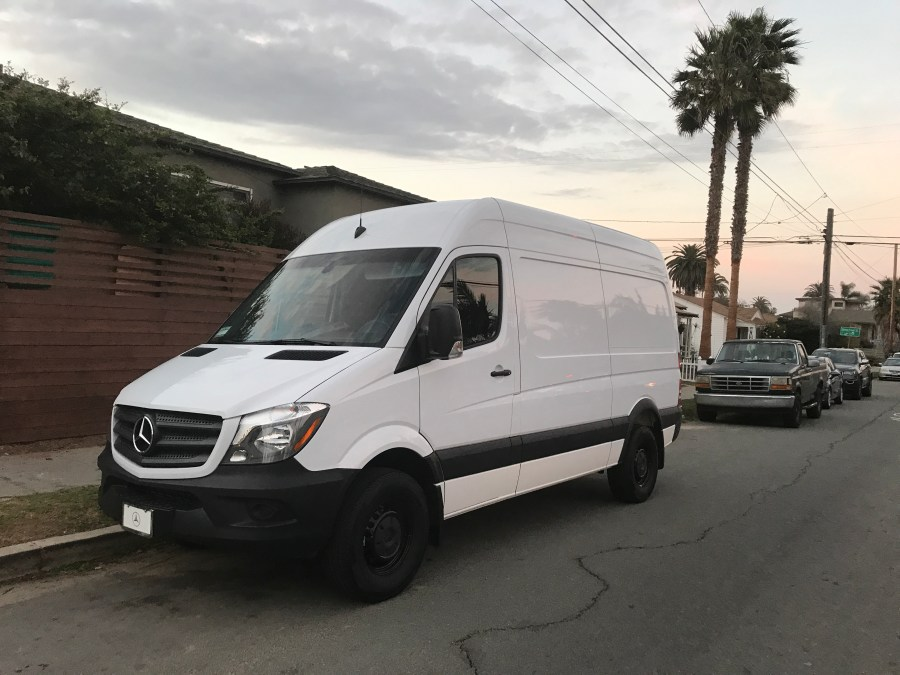 White sprinter van parked in the city