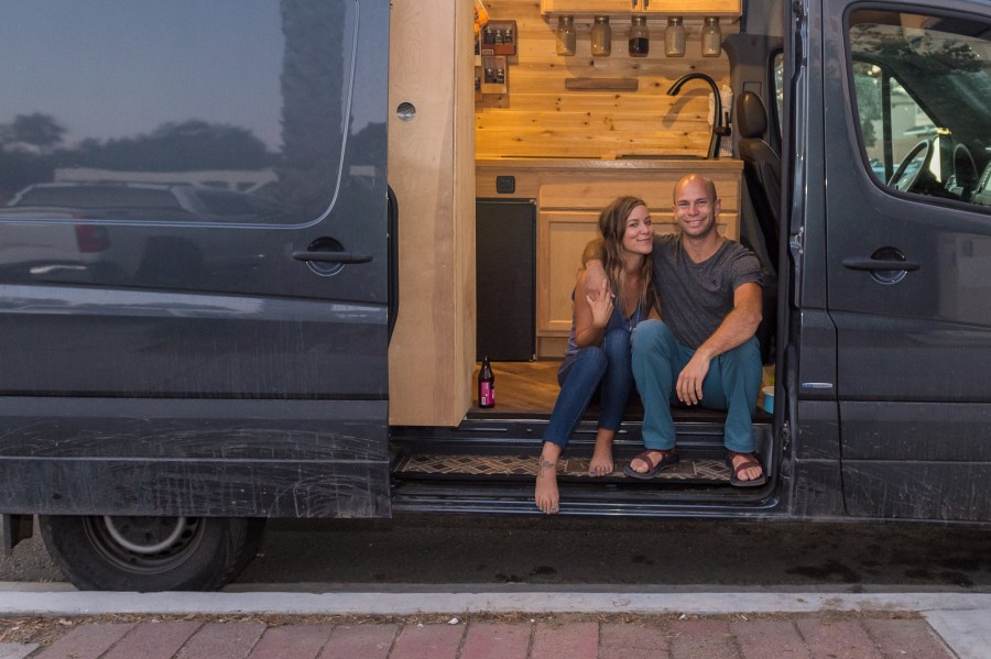two people sitting in a sprinter van that has been converted to a home