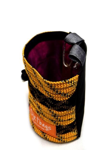 Top view of orange and black chalk bag with purple tie dye internal fleece