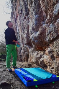 Jame sin green trousers looks at boulder problem with bright blue bouldering mat by his feet.