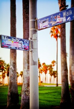 converging street signs on the venice boardwalk in california