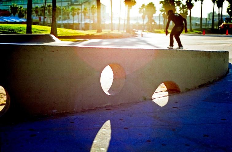 a skateboarder taking a morning ride at the venice boardwalk in california