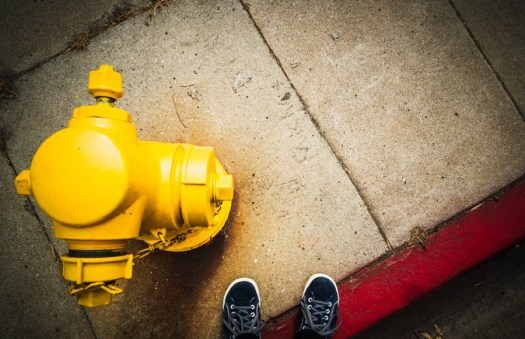 my blue suede shoes next to a yellow fire hydrant