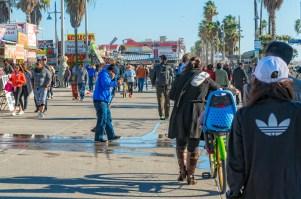 man sweeping water on the Venice boardwalk