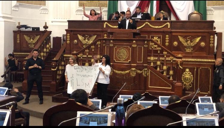 Ernesto Escobedo en tribuna, debajo, dos mujeres sostienen un cartel con el plan que propone para la enseñanza de LSM