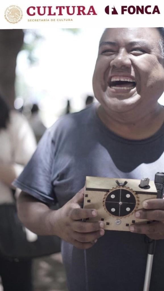 (Cartel que anuncia el Laboratorio con logos del FONCA y la Secretaría de Cultura. Un hombre joven está sonriendo y sostiene en sus manos una cámara de madera y un bastón blanco. )