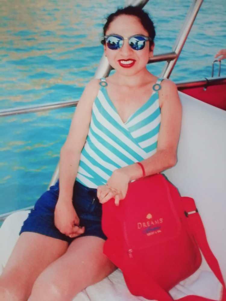 Foto de  Jazmín Martinez sonriente, con lentes oscuros, sentada en una embarcación., detrás se ve el mar.