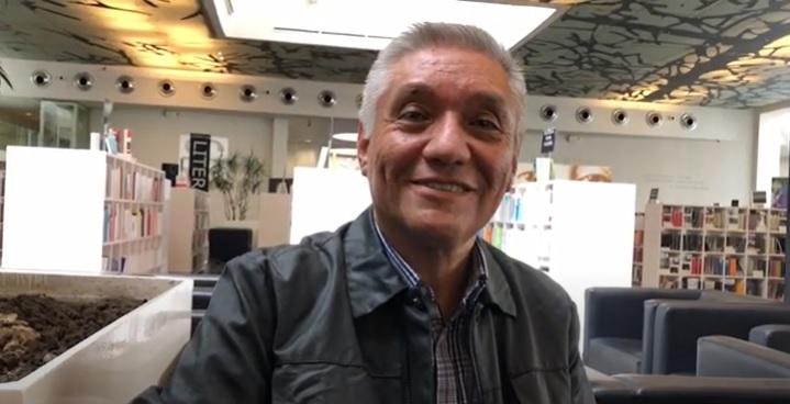 En la foto, el Dr. Enrique Garrido, sonriente. Detrás de él, los estantes de una librería.