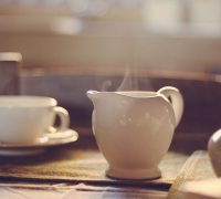 A white teapot sits on a table with a teacup in the background. Steam rises from the teapot.