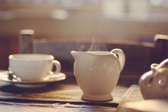 a white teapot sits on a breakfast table.  Steam slowly rises.