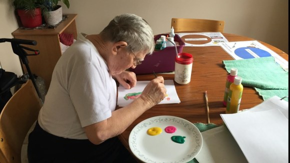 An older man sits at a kitchen table with art supplies  spread around him as he works on a painting.