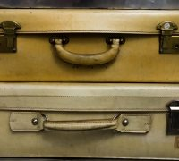 Four vintage suitcases are stacked on top of each other and fill the entire frame.