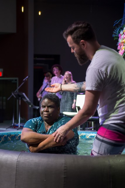 A Black woman kneels in a baptismal tank. A white man stands beside her preparing to baptize her.