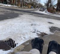 Dion's outstretched legs are visible as he takes a photo from his position sitting in his wheelchair. The sidewalk in front of him is fairly clear, but beyond the curb there is lots of snow and a drain in the street visible.There is a curb cut in front of him, leading down to the street.