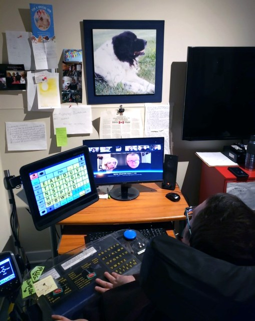 The camera is behind Ray and shows him sitting in his wheelchair using his computer.  A church service is on the screen.  His Dynavox computer is attached to his wheelchair tray and the alphabet is visible on the screen.  Ray has brown hair, and light skin.