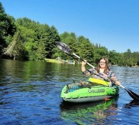 Sarah has long brown hair and glasses and is smiling as she paddles a kayak in a lake.