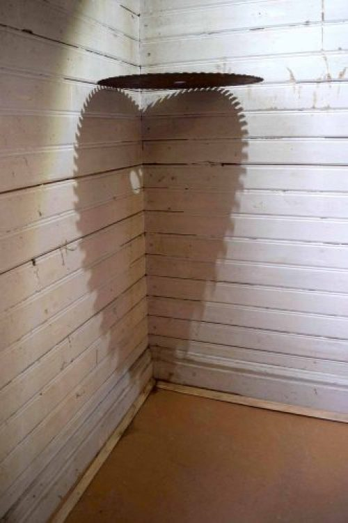 Photo of a suspended circular saw blade positioned against a wall to reveal a heart-shaped shadow.