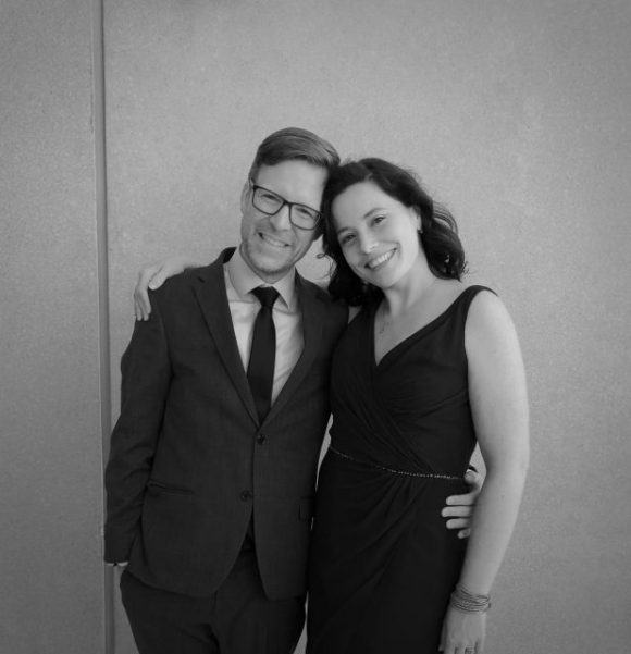 Carlo is wearing a suit, dark-framed glasses and is smiling while he has his arm around his wife Allyson who stands next to him.  She is wearing a black dress and is also smiling.