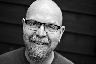 A black and white photo of Dion smiling into the camera.  He is a white man with a goatee, glasses, and no hair on his head.