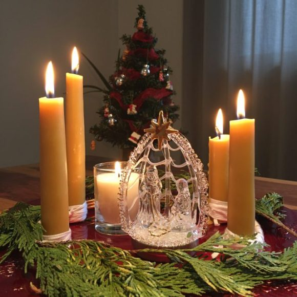An advent wreath sits on a table with a small glass nativity set in the centre  all five candles are lit  . There is a small Christmas tree in the background