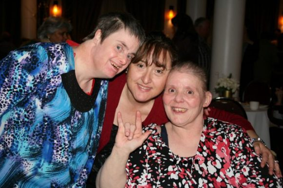 """Three white women lean close together and smile at the camera.  The woman on the left has down syndrome, and is standingthe woman on the right is making the """"I Love You"""" sign to the camera and is seated.  The woman in the middle has her arms around both other women and is drawing all three together."""