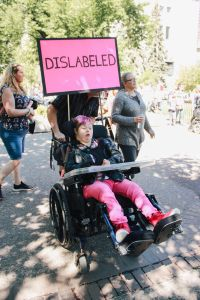 Female being pushed in wheelchair with sign that says Dislabeled