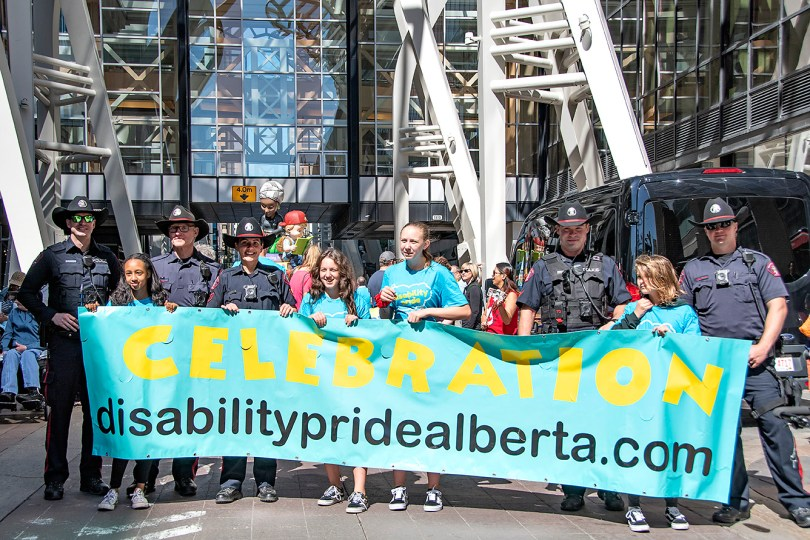 Police and younger people hold banner saying Celebration disabilitypridealberta.com