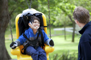 child with a disability on an accessible swing having fun with parent