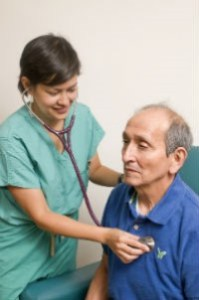 doctor examining her elderly patient with a stethoscope