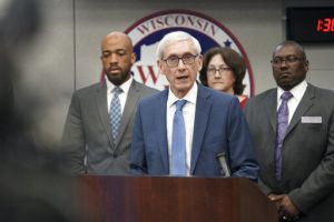 Governor Evers speaking at podium with people standing behind him