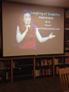 "An image of a projector screen showing an image of a woman holding a microphone doing stand-up with the text: ""Laughing at Disability Awareness with Nina G ninagcomedian.com"