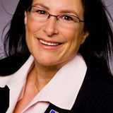 Photo of a woman with long brown hair and glasses.