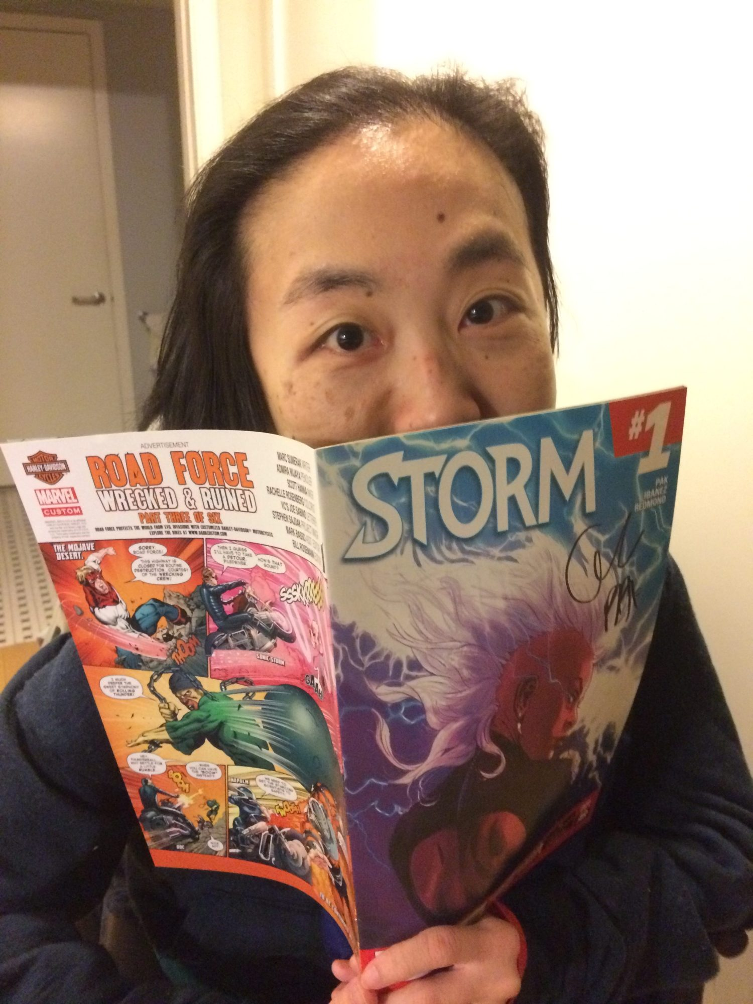 Asian American woman in a wheelchair wearing a navy hoodie. She is holding a comic book by Marvel, Storm #1, close to her face, covering her mouth.