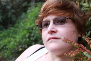 A woman with wavy red hair wearing tinted glasses staring at the camera. There are green bushes in the background.