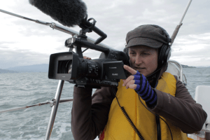 Photo of a woman bundled up in a hat, gloves and a jacket holding a camera while out on a boat in the middle of the ocean or a body of water.