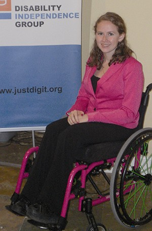 Picture of a woman with long curly hair in a bright pink jacket and black pants. She is sitting in a wheelchair and a poster behind her reads: Disability Independence Group
