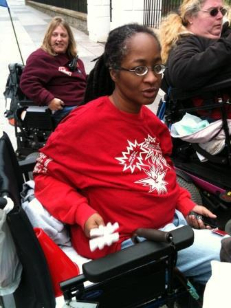 An African-American woman wearing eyeglasses and dressed in a long-sleeved red shirt. She is sitting in a wheelchair.