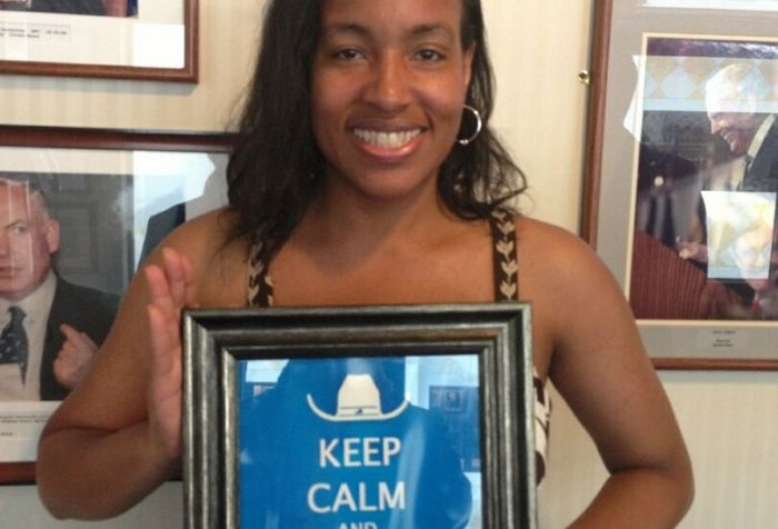An African-American woman with long hair holding a framed poster that says 'Keep Calm and Lead On.' She is smiling at the camera.