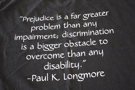 "Dark fabric with a quote printed on it in white: ""Prejudice is a far greater problem than any impairment; discrimination is a bigger obstacle to overcome than any disability."" --Paul K. Longmore"