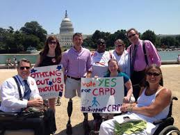 """Photo of 8 people with the Capitol building in the background in Washington, DC. Three people are using wheelchair users. Two people are holding signs that read: """"Nothing about us without us"""" and """"Vote Yes CRPD."""""""
