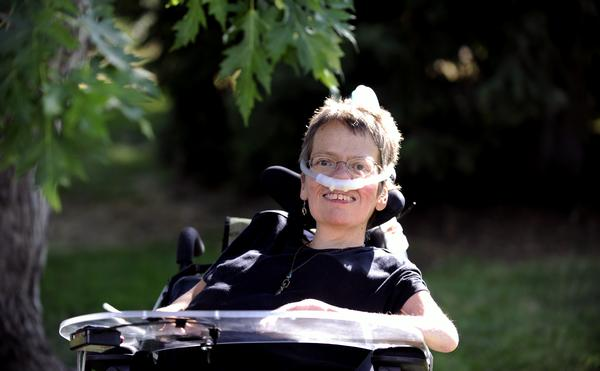 Woman in a wheelchair smiling and wearing a mask that goes around her nose. She is wearing glasses and a black t-shirt. She's smiling at the camera and the background is green grass and trees.