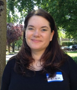 Image description: A woman with long brown hair, a black shirt, and a name tag written in Sharpie on her shirt stands outside near the trees, smiling at the camera.]
