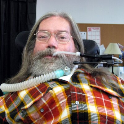 An older man with long gray hair and a full beard. He is wearing a plaid shirt and he uses a ventilator and wheelchair.