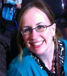 A white woman with glasses and long brown hair smiling at the camera. She is eating a turquoise jacket and a black necklace.