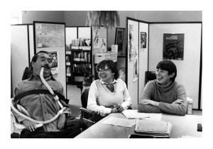 A black-and-white photo of three people sitting at a table smiling and looking at one another. On the left is a man in a wheelchair with a ventilator. In the middle is a woman in a wheelchair and on the right is another woman seated in a chair.