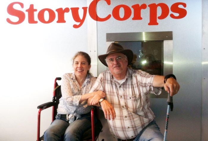 Picture outside a metal recording booth with a sign in the background that reads 'StoryCorps' in the front is a middle-aged woman in a wheelchair. She is clasping the arm of an older man who is next to her, bending his knees halfway down. He is wearing a hat and holding on to a walking stick.