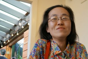 Asian-American woman with long black hair and glasses. She is wearing a floral print shirt.