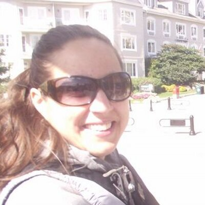 A white woman with long brown hair in a pony tail. She is wearing sunglasses and smiling at the camera.