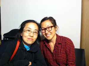 Two Asian American women sitting next to each other both smiling. Both are wearing glasses.